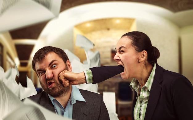 La donna d'affari grida al giovane uomo d'affari e lo picchia