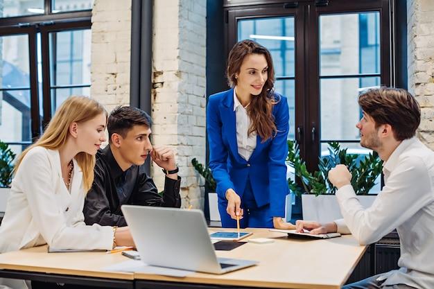 Imprenditrice mostra grafico su tablet ai colleghi