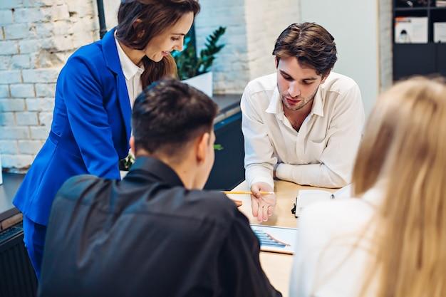 Imprenditrice che mostra il grafico sul tablet ai colleghi al tavolo in ufficio