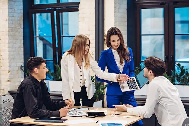 Donna d'affari che mostra il suo computer portatile ai suoi colleghi