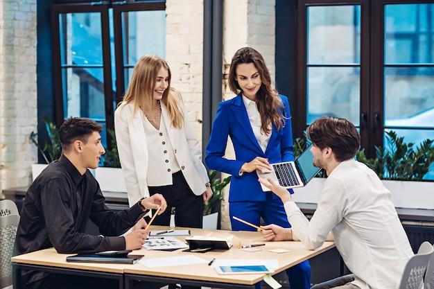 Donna di affari che mostra sul computer portatile ai colleghi