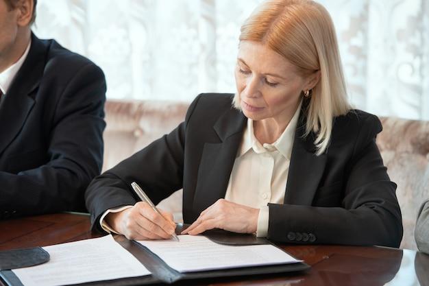 Donna d'affari che firma la carta mentre è seduta accanto al delegato straniero