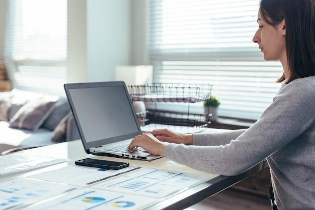 Imprenditrice seduta al suo posto di lavoro in ufficio, digitando, guardando lo schermo del laptop.