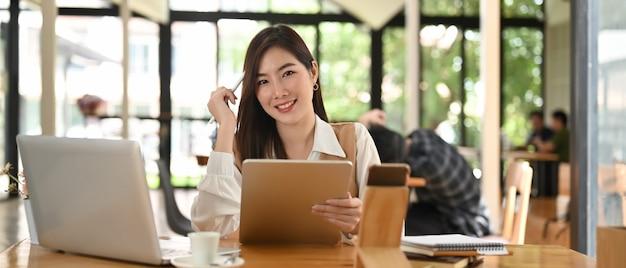Donna di affari che si siede nella sala riunioni mentre si lavora con tablet e laptop sulla scrivania in legno.