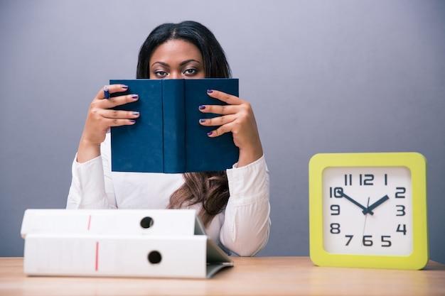 Imprenditrice seduta al tavolo e coprendosi il viso con il libro