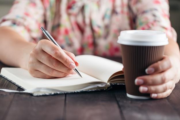 Donna di affari che si siede con una tazza di caffè contro