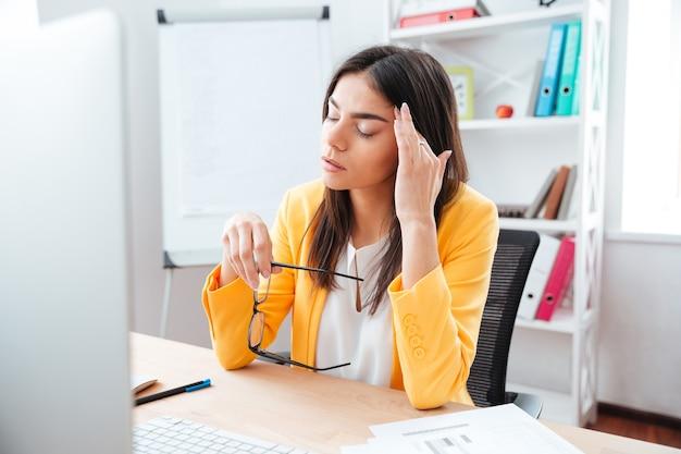 Donna d'affari seduta con mal di testa sul posto di lavoro in ufficio
