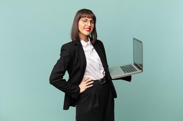 Donna d'affari che sorride felicemente con una mano sull'anca e un atteggiamento fiducioso, positivo, orgoglioso e amichevole