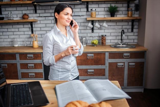 Imprenditrice stand in cucina e parlare al telefono.