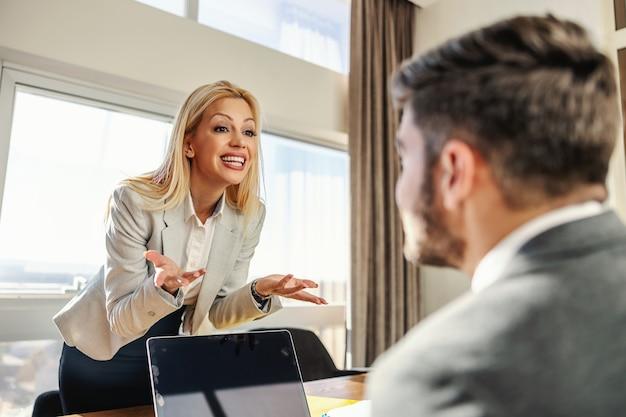 Donna d'affari in piedi in ufficio e in disaccordo con il suo collega che è seduto in abiti eleganti davanti a un laptop