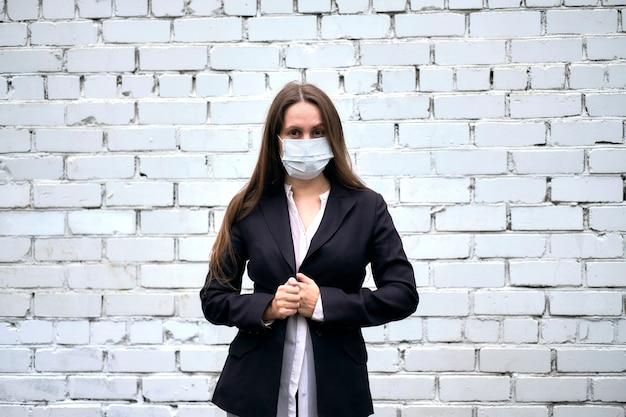 La donna di affari sta in una maschera e una giacca contro un muro di mattoni bianchi