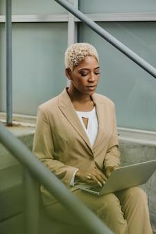 Imprenditrice sui gradini usando il suo laptop
