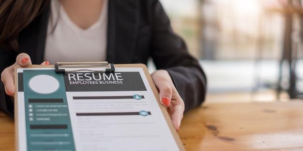 La donna d'affari invia il curriculum al datore di lavoro per rivedere le informazioni sulla domanda di lavoro sulla scrivania, presenta la possibilità per l'azienda di concordare con la posizione del lavoro.