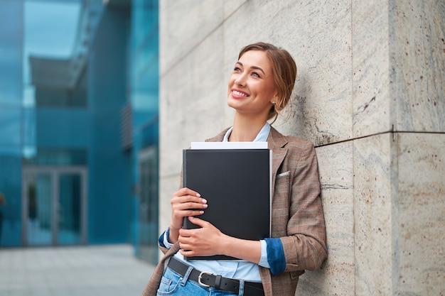 Imprenditrice donna d'affari di successo in piedi all'aperto edificio aziendale esterno. pensiv caucasica fiducia professionale donna d'affari mezza età