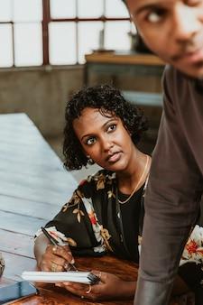 Imprenditrice prendendo appunti in una riunione