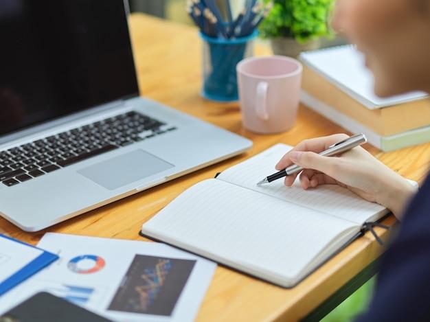 Donna di affari che prende appunti sul taccuino sul tavolo di lavoro con il computer portatile, relazione finanziaria, tazza di caffè. avvicinamento