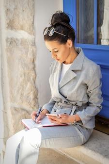 Donna d'affari che prende appunti mentre è seduta sulle scale