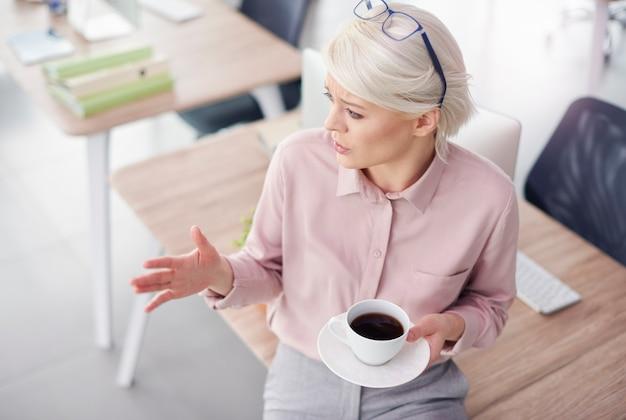 Imprenditrice parlando e gesticolando durante la pausa caffè
