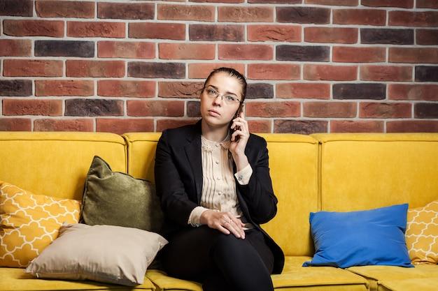 Una donna di affari che parla su un telefono cellulare, donna che parla sul telefono in ufficio, ritratto della donna di affari che parla sul telefono cellulare, concetto di affari