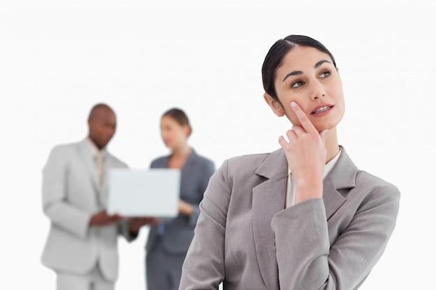 Imprenditrice nei pensieri con i colleghi dietro di lei
