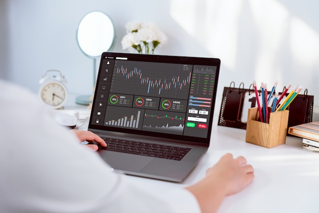 Commerciante della donna di affari che guarda computer con la linea della candela di analisi dei grafici