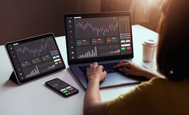 Commerciante della donna di affari che considera computer portatile e compressa, smartphone con la linea della candela di analisi dei grafici nella stanza dell'ufficio