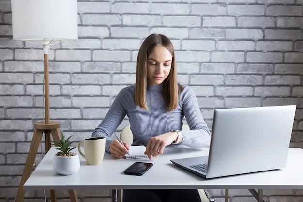 Imprenditrice cercando di rispettare la scadenza in ufficio a casa. bella donna casuale che lavora ad un computer portatile.