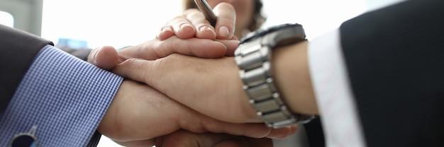 La donna di affari e due uomini d'affari hanno piegato le mani insieme in primo piano dell'ufficio. conclusione del concetto di accordi internazionali.