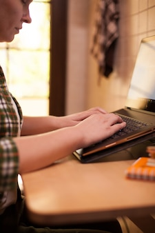 Donna d'affari che digita sulla tastiera del laptop durante il covid-19 da casa.