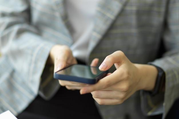 La donna d'affari usa lo smartphone per il lavoro a distanza, il contatto d'affari. le mani delle donne usano un telefono cellulare per lo shopping online, i social network. immagine ravvicinata.