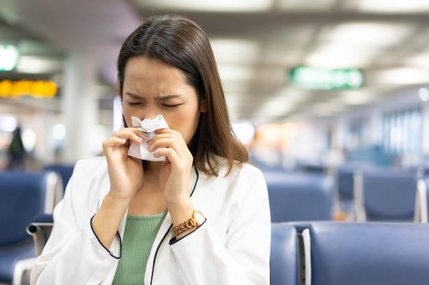 La donna di affari e usa la carta velina per scorrere sul suo tubo flessibile nel cancello dell'aeroporto per il concetto di coronavirus
