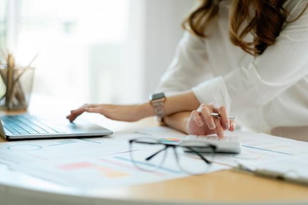 Donna d'affari che utilizza la calcolatrice per l'analisi del piano di marketing contabile calcola il rapporto finanziario