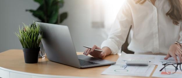 Donna d'affari che utilizza calcolatrice e computer portatile per l'analisi del piano di creazione, contabile calcola il rapporto finanziario, computer con grafico grafico. concetto di affari, finanza e contabilità.