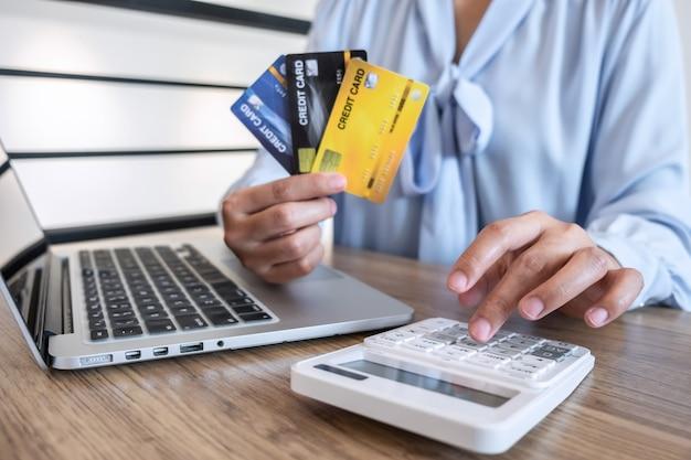 Donna di affari che utilizza computer portatile e che tiene la carta di credito per il pagamento del codice di sicurezza di acquisto online dell'esposizione di acquisto della visualizzazione della pagina e dell'immissione delle informazioni della carta