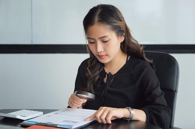 Imprenditrice utilizzando ingrandimento per rivedere il bilancio annuale