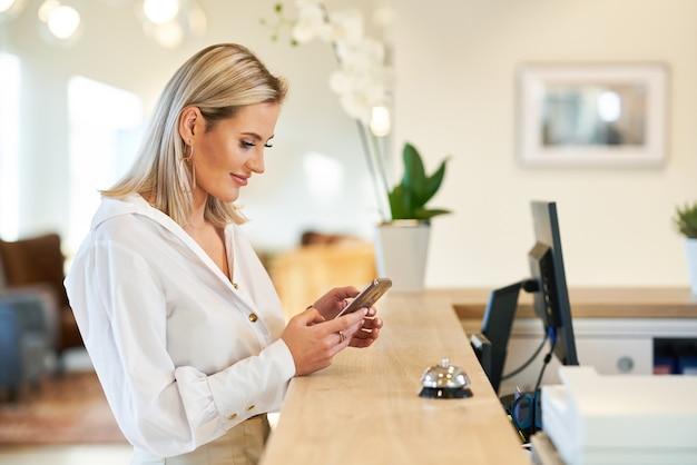 Imprenditrice utilizza lo smartphone alla reception dell'hotel