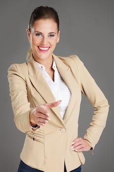 Donna d'affari in posa di benvenuto su sfondo grigio