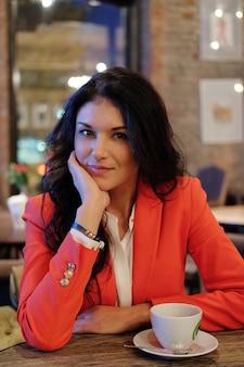 Imprenditrice in camicia bianca e giacca rossa a pranzo nella caffetteria.