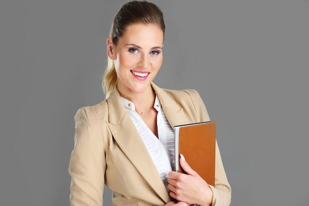 Donna d'affari con agenda su sfondo grigio