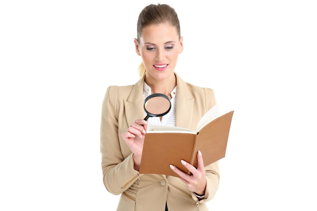 Donna d'affari con agenda e lente di ingrandimento su sfondo bianco