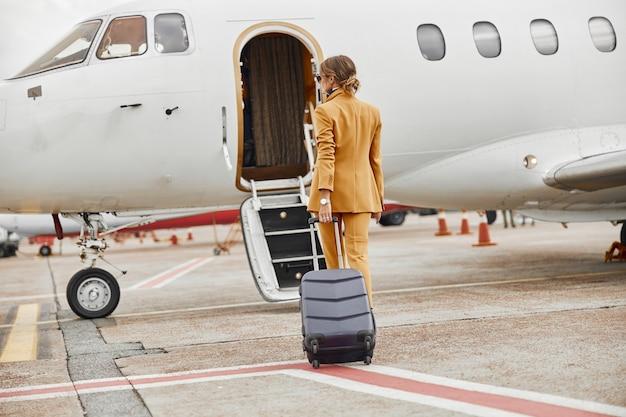 Imprenditrice con bagaglio a piedi al jet aereo privato. aereo passeggeri moderno con scaletta. vista posteriore della donna indossa abito formale e occhiali. aviazione civile. concetto di viaggio aereo e affari