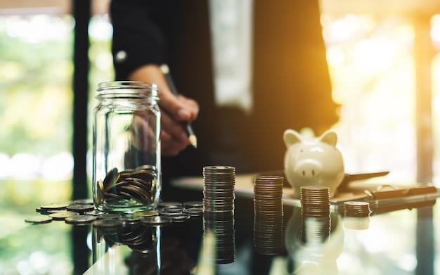La donna di affari con le monete impila, un barattolo di vetro dei soldi e un porcellino salvadanaio sulla tavola per il risparmio e il concetto finanziario