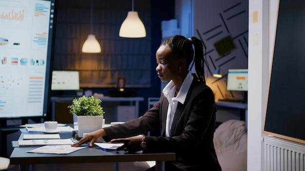 Donna d'affari con la pelle scura che lavora sodo a tarda notte nella sala riunioni dell'ufficio