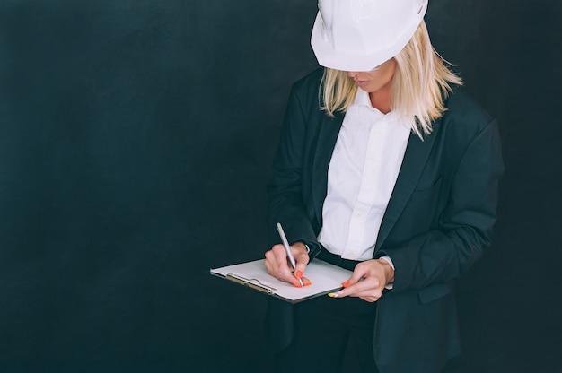 Imprenditrice con documenti in mano e un casco da costruzione in testa.