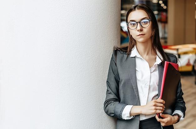 Imprenditrice con documenti per il lavoro. ragazza dell'allievo con cartelle con documentazione