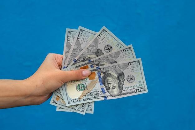 Imprenditrice con dollari isolati su blu. concetto di finanza