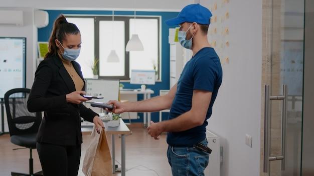 Donna d'affari con maschera facciale contro il coronavirus che paga l'ordine di cibo da asporto con telefono senza contatto