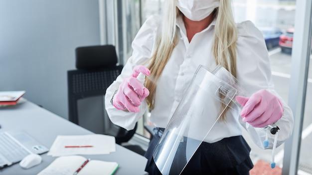 Imprenditrice con maschera facciale utilizzando disinfettante per le mani durante la pulizia della sua visiera in ufficio. donna che indossa una maschera protettiva. protezione dal coronavirus.