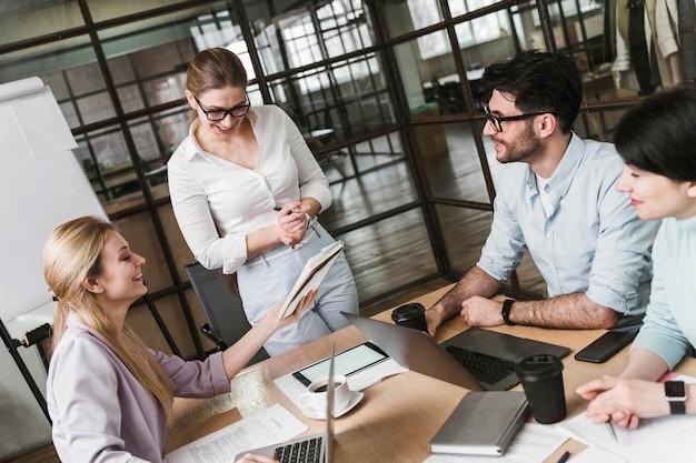 Imprenditrice con gli occhiali durante un incontro professionale con i suoi colleghi