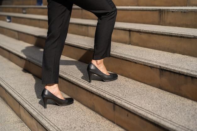 Imprenditrice con scarpe tacco alto salendo sulle scale della città